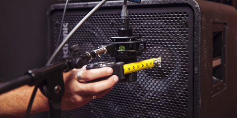 LEWITT microphone is getting positioned in front of bass amp