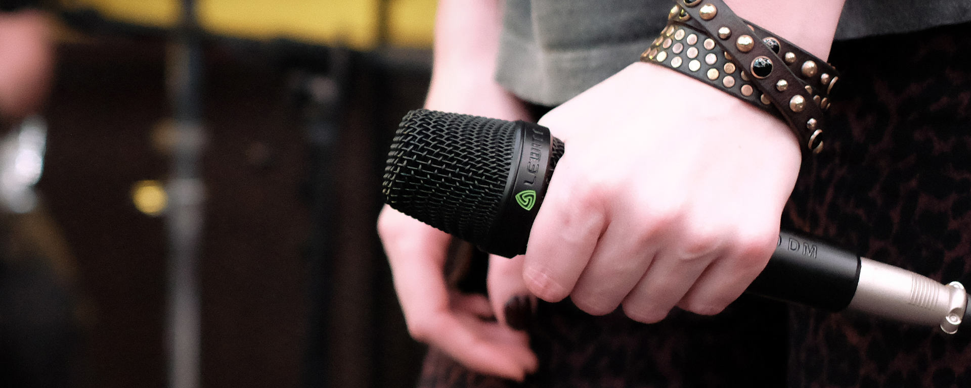 A woman's hand holding an MTP 250 microphone during a performance